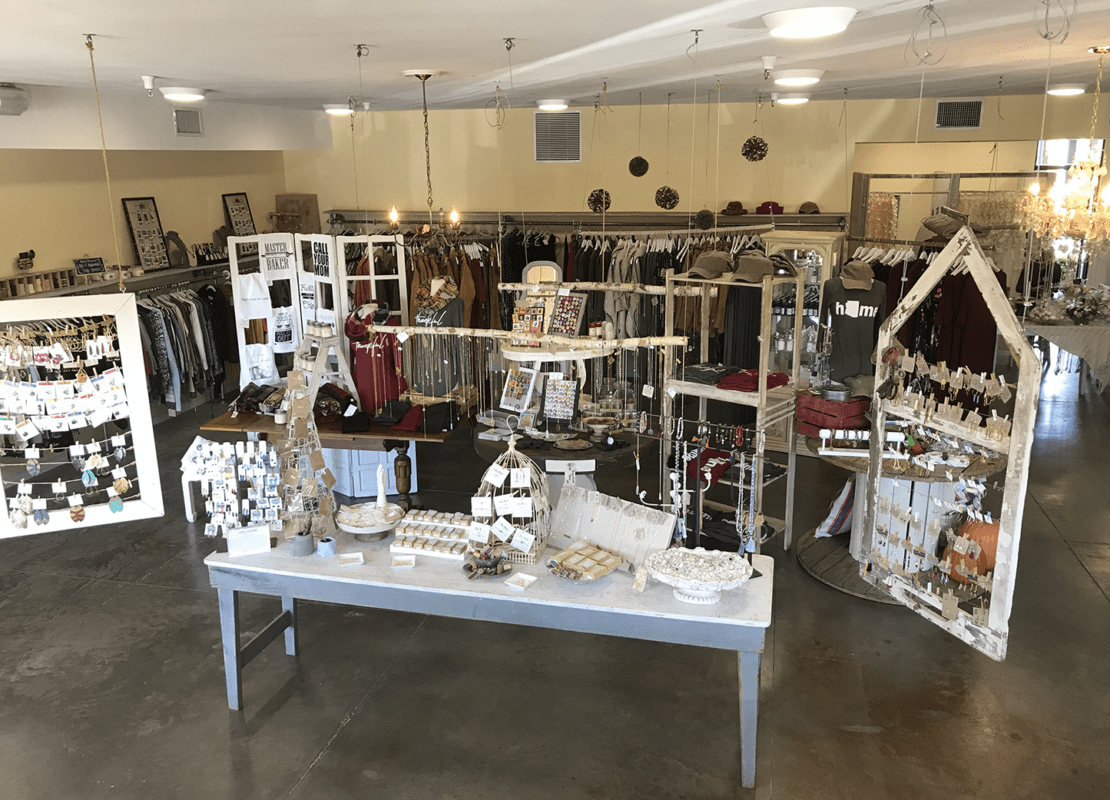 Interior of Poor Little Rich Girl located in Phoenix Arizona with a grey and white table with soaps, necklaces, earrings, clothing in the background on racks.